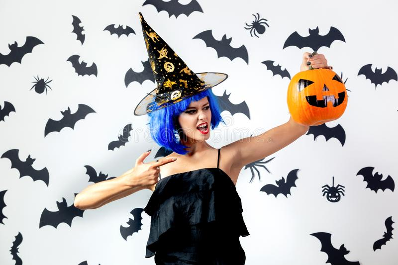 Funny young woman in a blue wig and witch`s hat holds Halloween pumpkin on a white background with black bats and royalty free stock photography