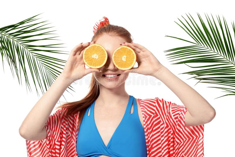 Funny young woman with citrus fruit and palm leaves on white background stock image