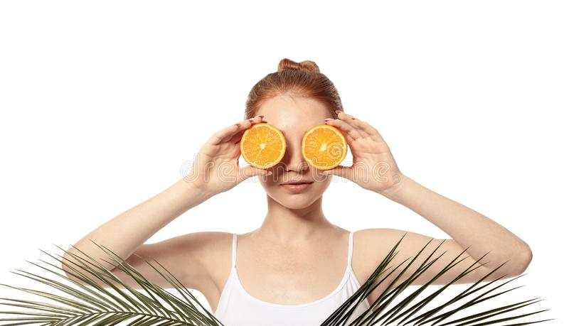 Funny young woman with citrus fruit and palm leaves on white background stock images