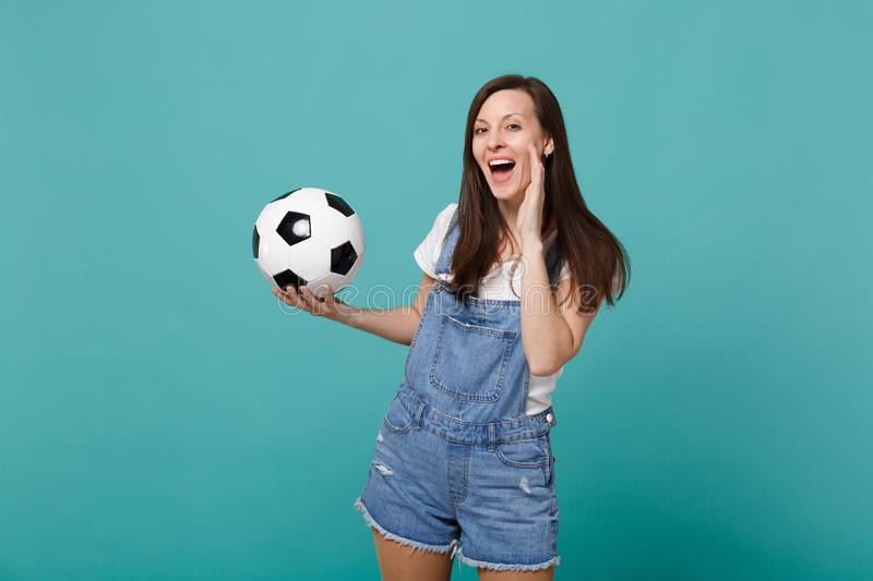 Funny young woman football fan cheer up support favorite team with soccer ball speaking with hand gesture isolated on. Blue turquoise background in studio royalty free stock photo