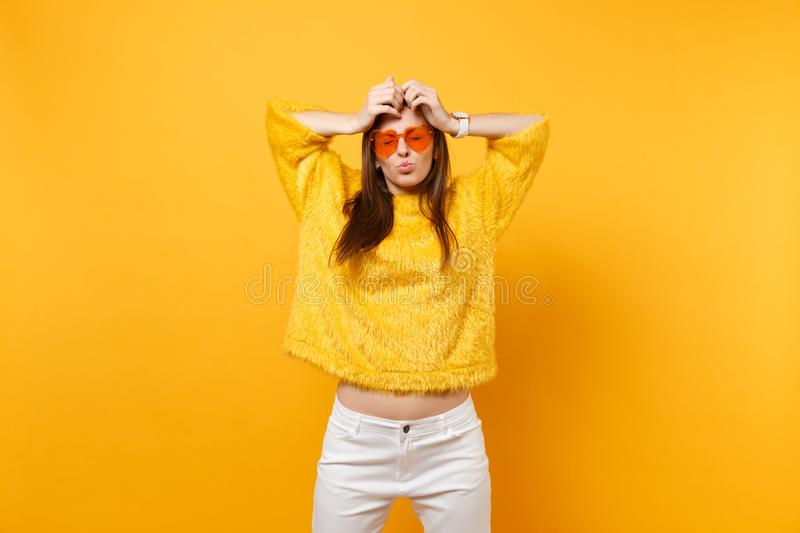 Funny young woman in fur sweater heart orange glasses fool around blowing lips putting hands on head isolated on bright stock photos
