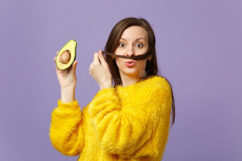 Funny young woman in fur sweater keeping hair like mustache, holding half of fresh ripe avocado isolated on violet stock images