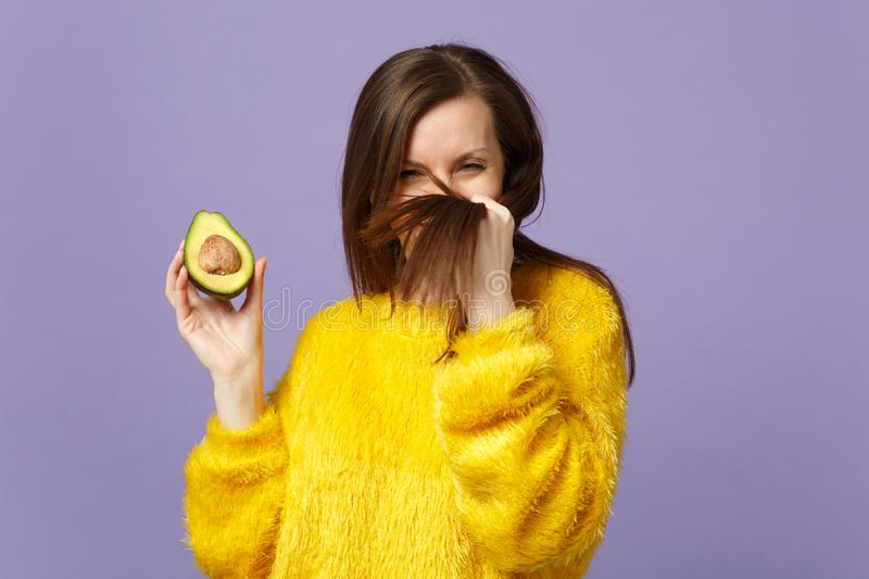 Funny young woman in fur sweater touching hair holding in hand half of fresh ripe green avocado  on violet. Pastel background. People vivid lifestyle relax royalty free stock images