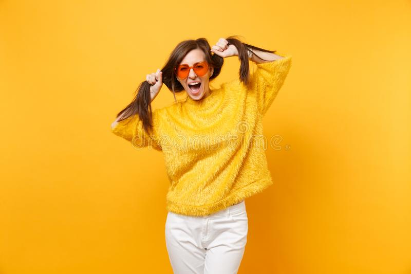 Funny young woman in fur sweater, white pants and heart orange glasses holding hair like ponytails isolated on bright. Yellow background. People sincere stock image