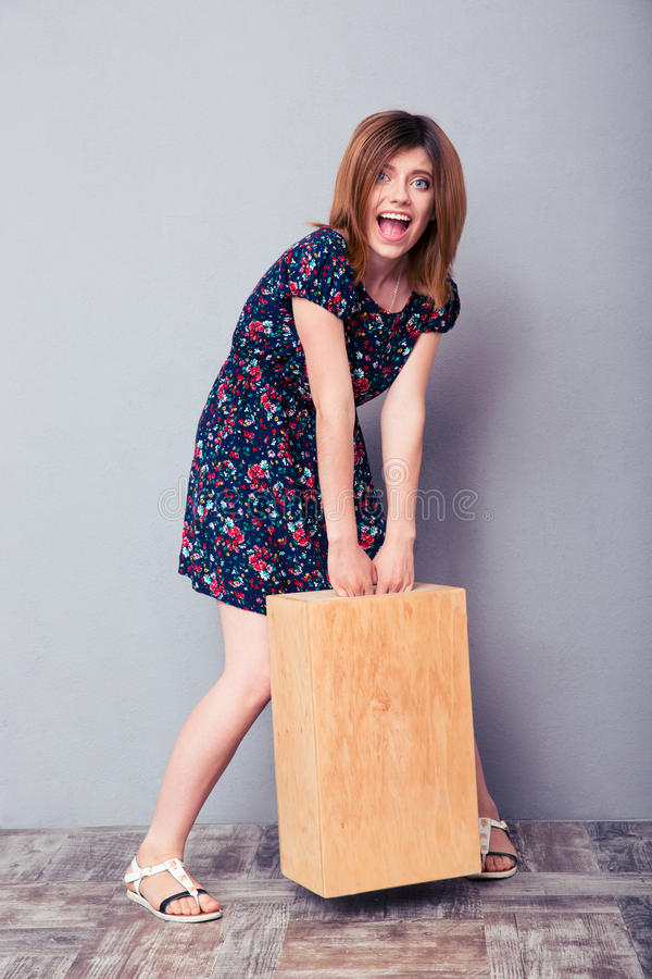 Funny young woman holding wooden box stock photography