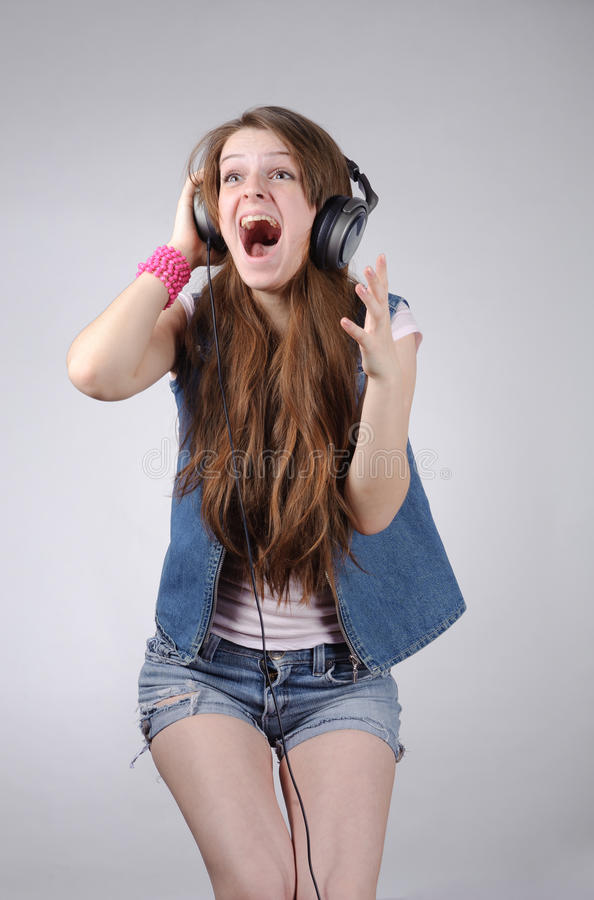 Funny young woman in jeanswear listening to music. Funny grimacing young woman with long hairs and headphones in jeanswear standing on grey royalty free stock image