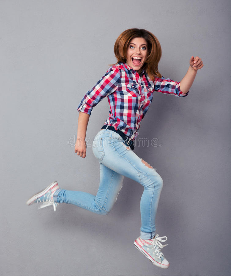 Funny young woman jumping. Over gray background and looking at camera royalty free stock images