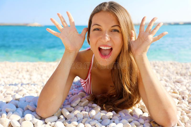 Funny young woman playing lying on pebbles beach. Close up portrait of happy girl on her travel holidays royalty free stock photo