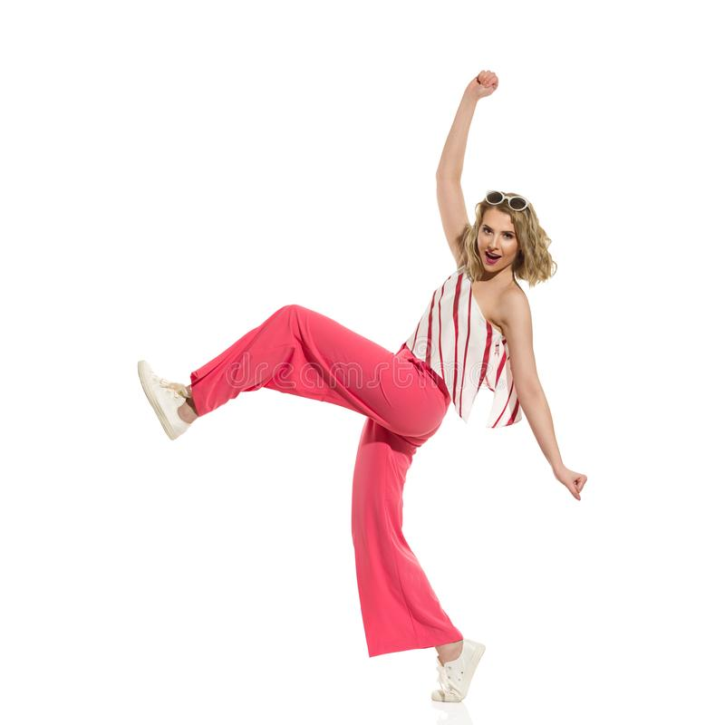 Funny Young Woman In Red Wide Leg Trousers Is Walking  With Arms Outstretched. Young woman in red wide leg trousers and striped top is funny walking with arms stock photos