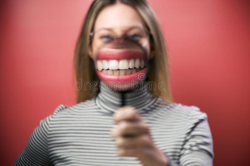 Funny young woman showing her mouth trought magnifying glass over pink background. Portrait of funny young woman showing her mouth trought magnifying glass over royalty free stock photo