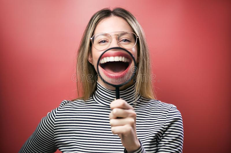 Funny young woman showing her mouth trought magnifying glass over pink background royalty free stock images