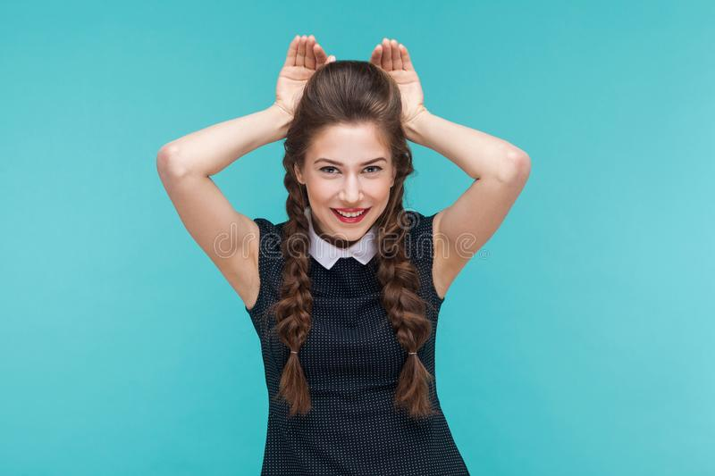 Funny young woman showing rabbit sign and smile. royalty free stock photos