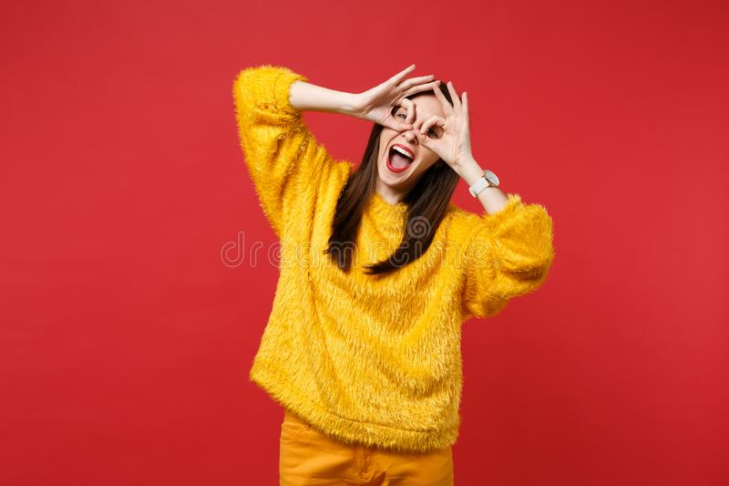 Funny young woman in yellow fur sweater holding hands near eyes, imitating glasses or binoculars isolated on bright red royalty free stock photo