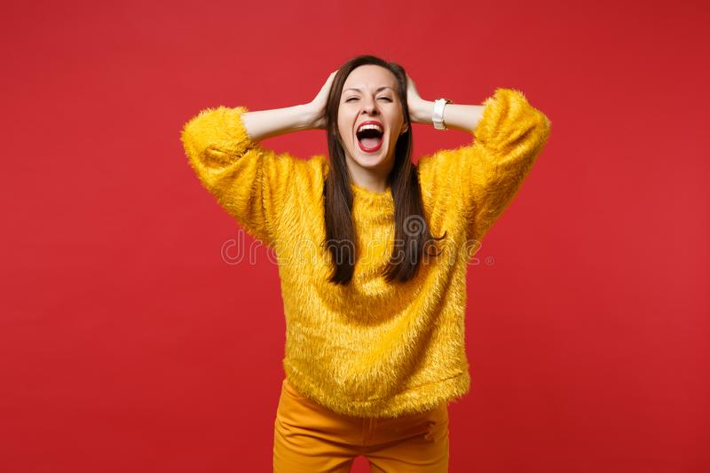 Funny young woman in yellow fur sweater keeping mouth wide open, clinging to head isolated on bright red wall background. In studio. People sincere emotions stock images