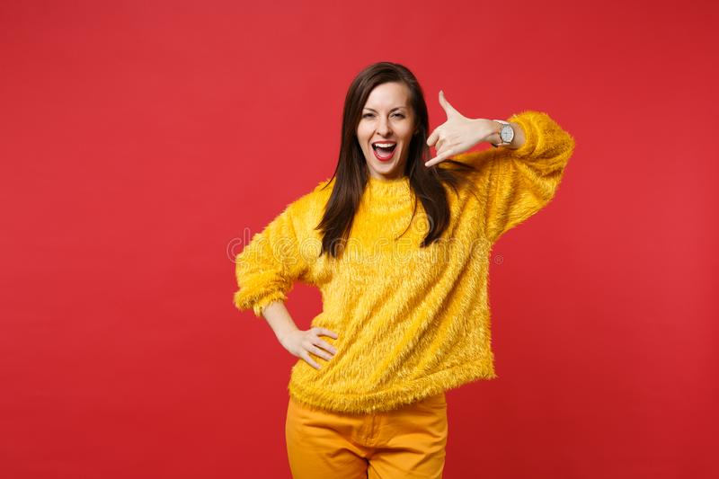 Funny young woman in yellow fur sweater keeping mouth wide open, doing phone gesture like says call me back isolated on. Red background. People sincere emotions stock image
