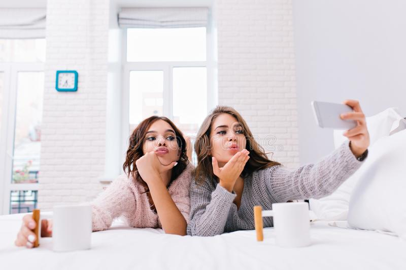 Funny young women in cozy soft sweaters making selfie portrait on bed. Joyful girls having fun, sending a kiss, drinking royalty free stock photography