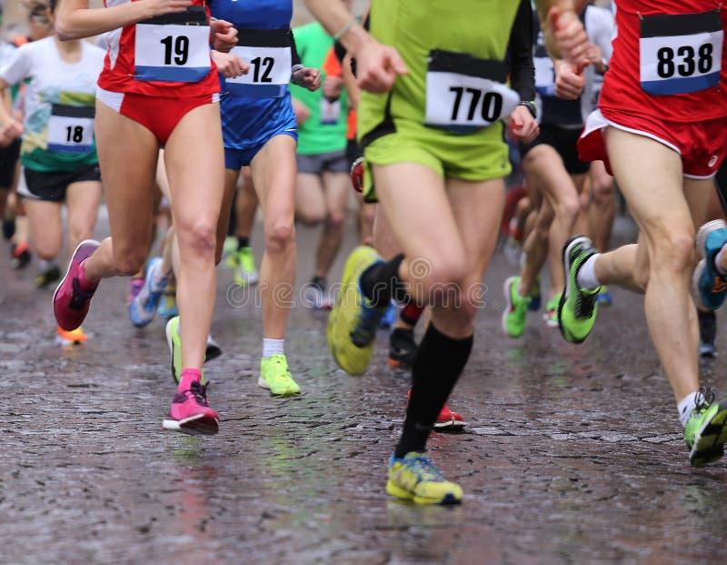 Funzionamenti degli atleti durante la maratona piovosa fotografia stock