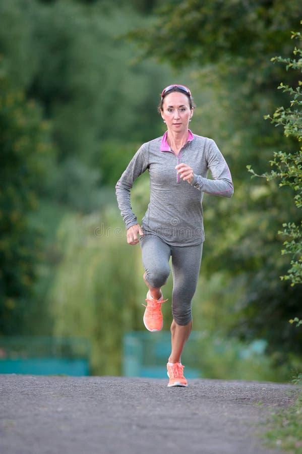 Funzionamenti dell'atleta femminile che si avvicinano al parco della città Eseguire il outd della donna fotografia stock libera da diritti