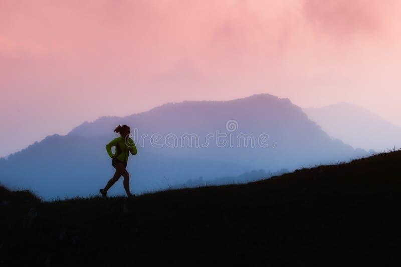 Funzionamenti della ragazza di sport nelle montagne da solo immagine stock libera da diritti