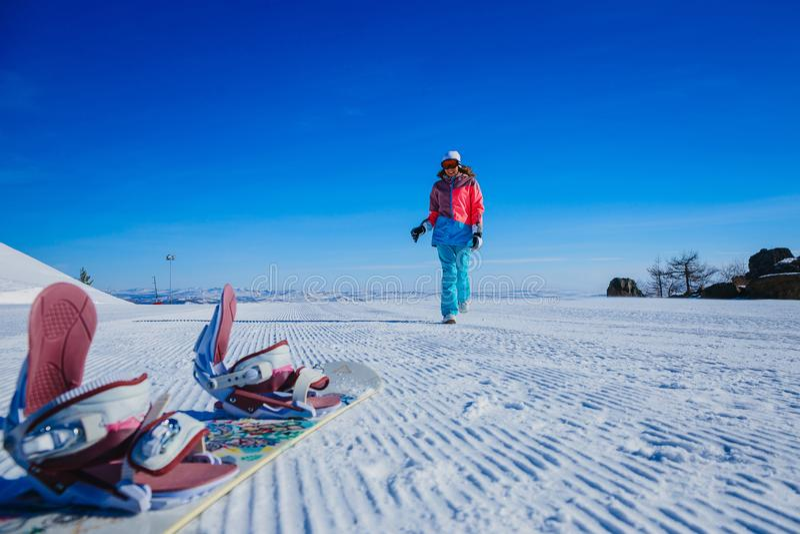 Funzionamenti sul pendio, stivali della donna sullo snowboard immagini stock