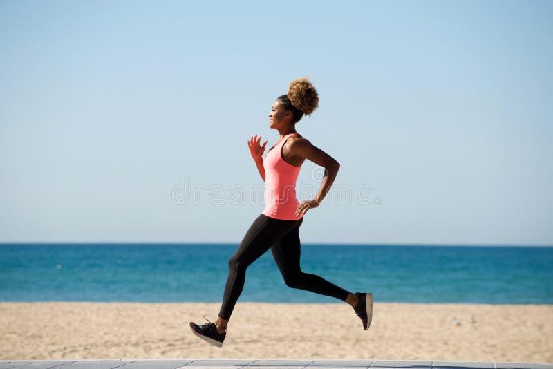 Funzionamento africano sano integrale della donna lungo la spiaggia nella mattina immagini stock libere da diritti
