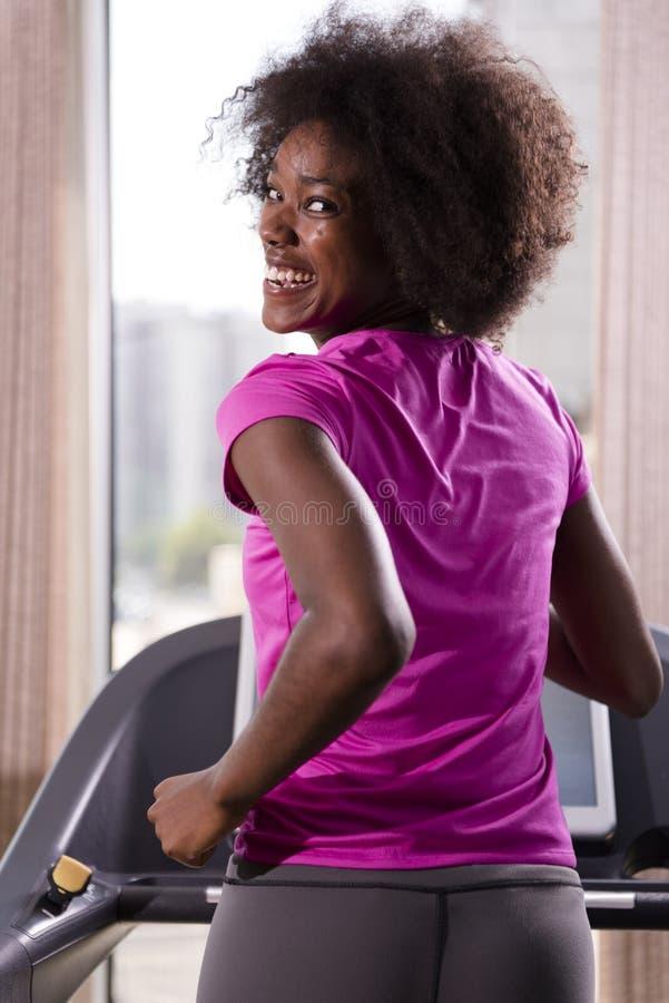 Funzionamento afroamericano della donna su una pedana mobile fotografie stock libere da diritti
