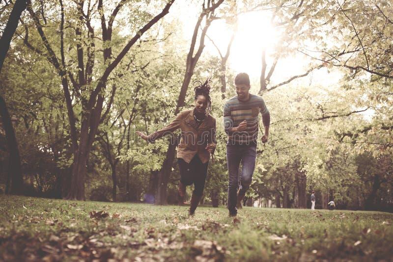 Funzionamento afroamericano felice delle coppie e prendere nel parco immagini stock libere da diritti