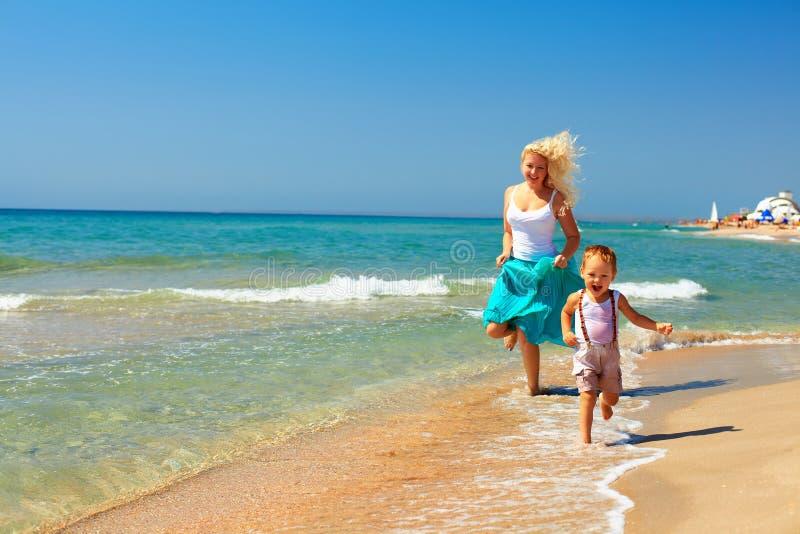 Funzionamento allegro del bambino e della madre in spuma sulla spiaggia fotografia stock libera da diritti