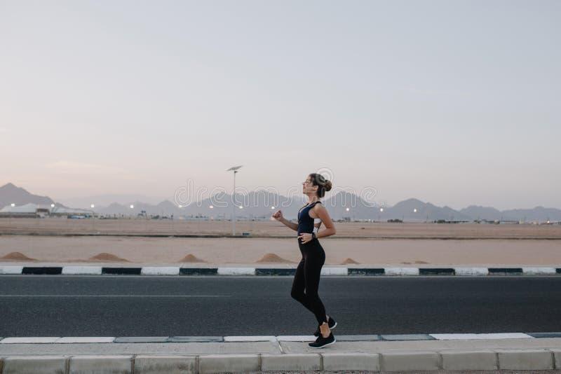Funzionamento, allenamento sulla strada nel primo mattino di bella donna allegra Addestramento di forte sportiva, energia, motiva immagini stock