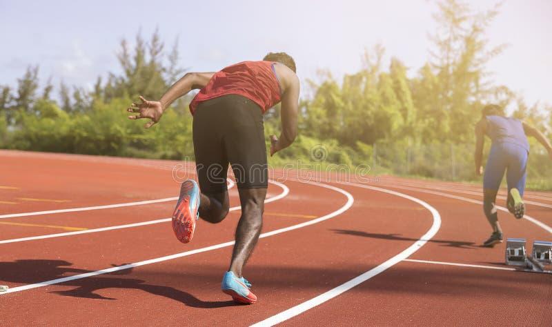 Funzionamento atletico del giovane sulla pista di corsa con il fondo di verde del bokeh fotografia stock