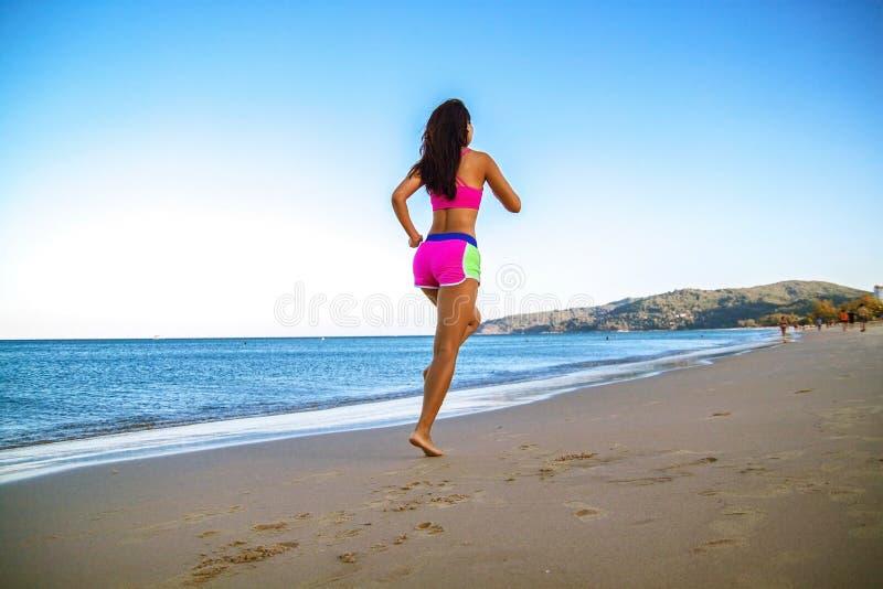 Funzionamento atletico della donna di forma fisica sulla spiaggia Allenamento esterno fotografie stock