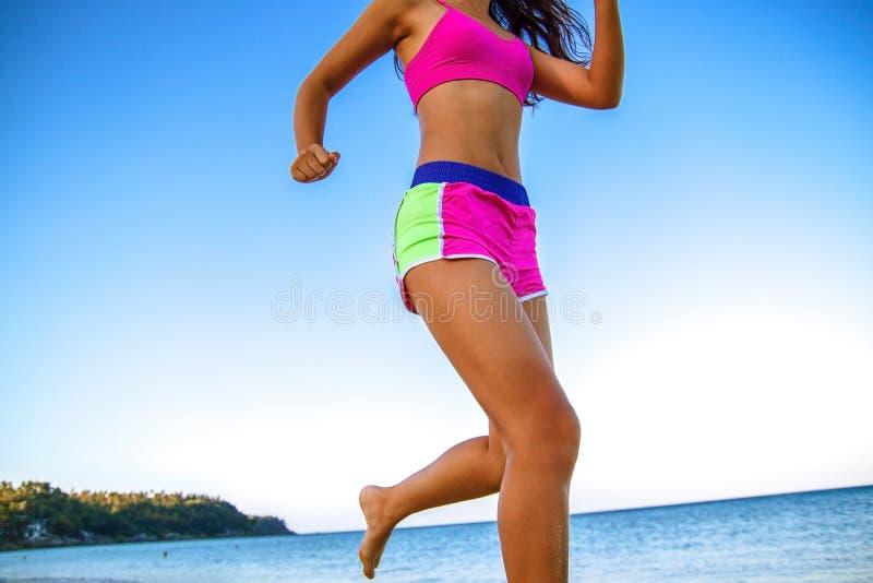 Funzionamento atletico della donna di forma fisica sulla spiaggia Allenamento esterno immagini stock
