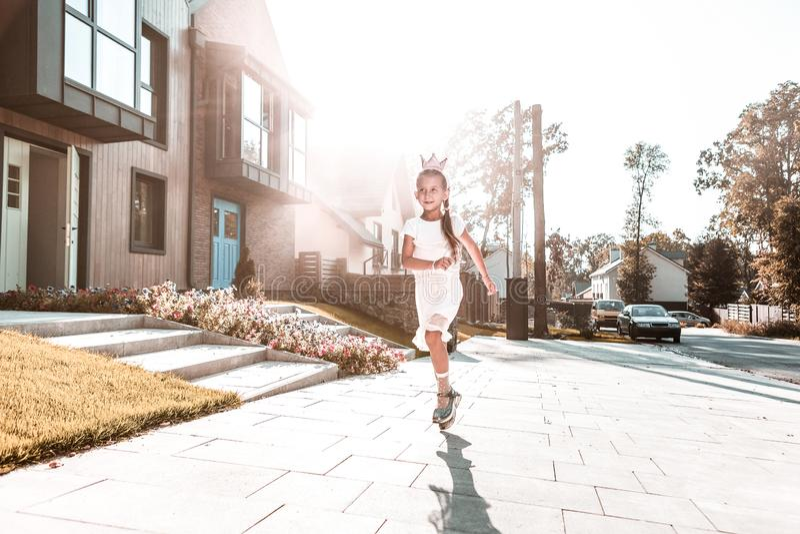 Funzionamento bianco d'uso del vestito da piccola principessa sveglia vicino alla sua casa fotografia stock