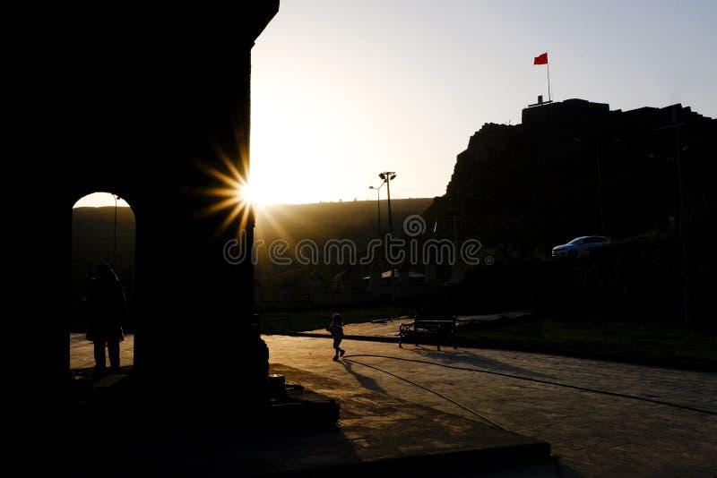 Funzionamento del bambino attraverso il quadrato al tramonto contro la luce fotografia stock
