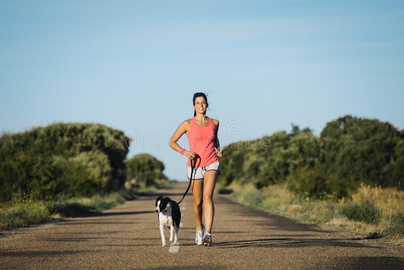 Funzionamento del cane e della donna sulla strada campestre fotografia stock libera da diritti