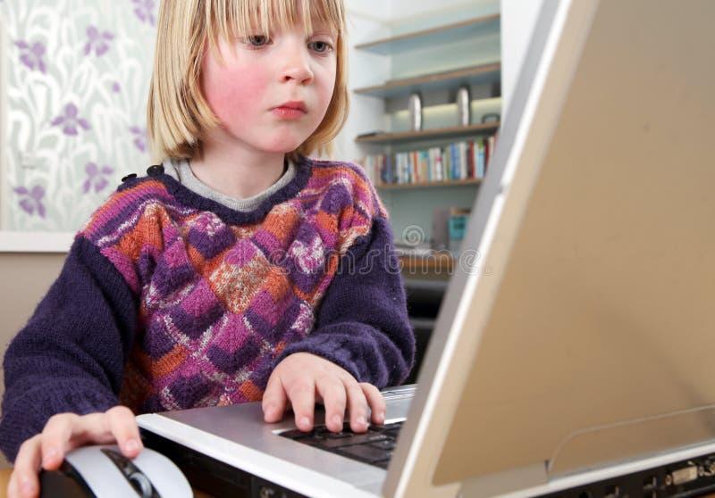 Funzionamento del computer portatile del bambino fotografia stock