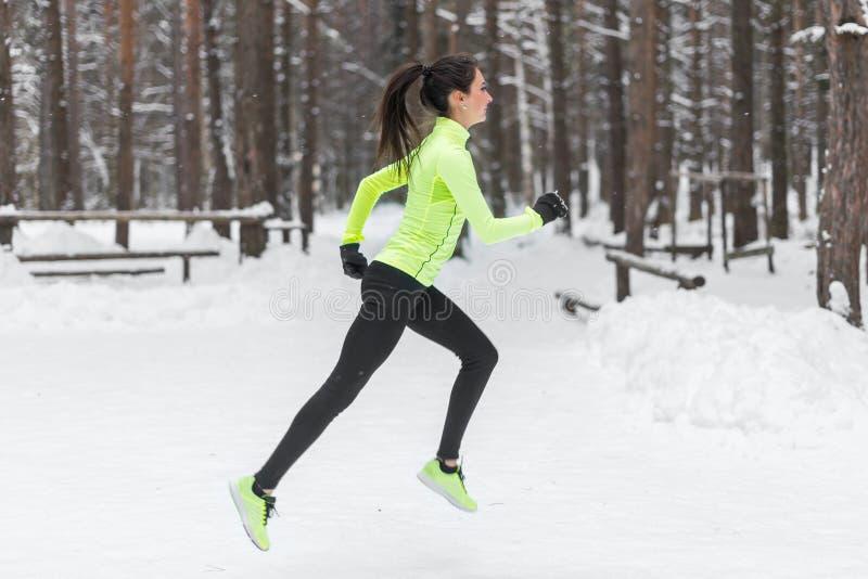 Funzionamento del corridore della donna dell'atleta in tempo di nevicata freddo Pareggiare maratona di cardio addestramento della fotografia stock