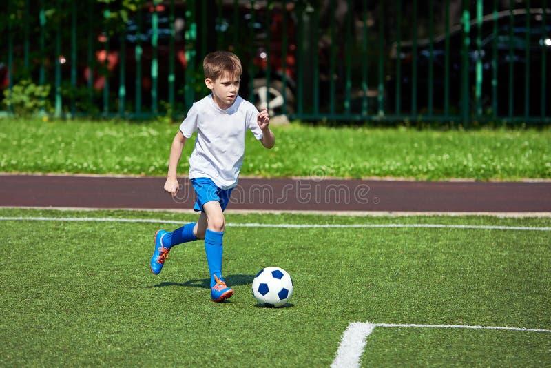 Funzionamento del giocatore di football americano del ragazzo con la palla su prato inglese verde immagine stock