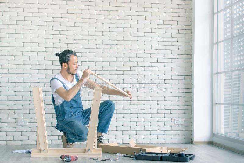 Funzionamento del giovane come tuttofare, tavola di legno di montaggio con equipm immagine stock
