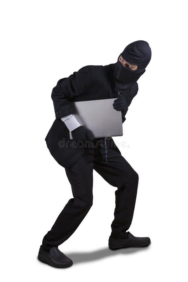 Funzionamento del ladro con il computer portatile isolato fotografia stock
