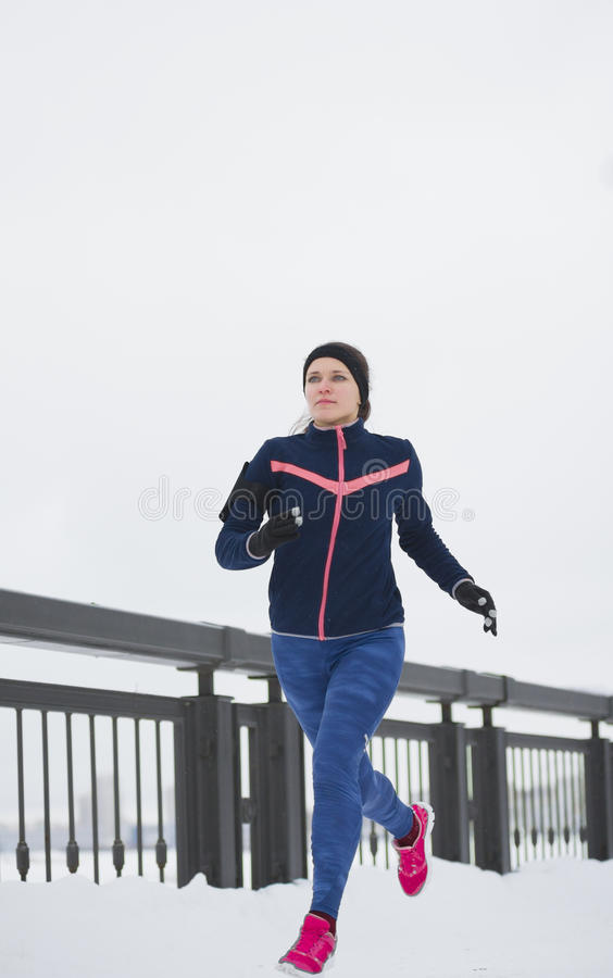 Funzionamento del modello di forma fisica della giovane donna alla passeggiata di inverno della neve fotografie stock libere da diritti