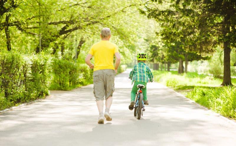Funzionamento del padre con il ragazzino, che guida una bici fotografia stock libera da diritti