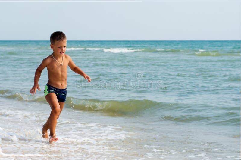 Funzionamento del ragazzino di estate alla spiaggia del mare fotografie stock libere da diritti