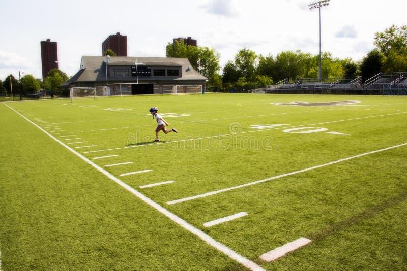 Funzionamento del ragazzo su un campo di football americano fotografia stock
