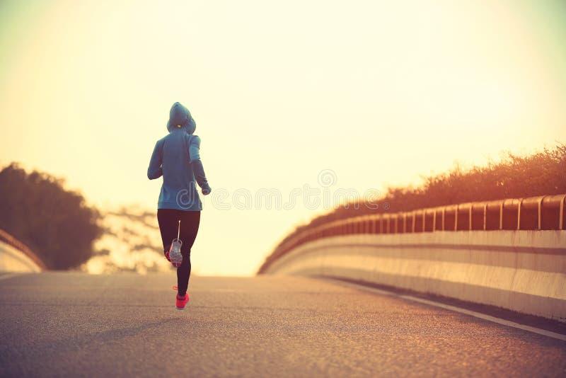 Funzionamento dell'atleta del corridore della donna di forma fisica alla strada immagini stock