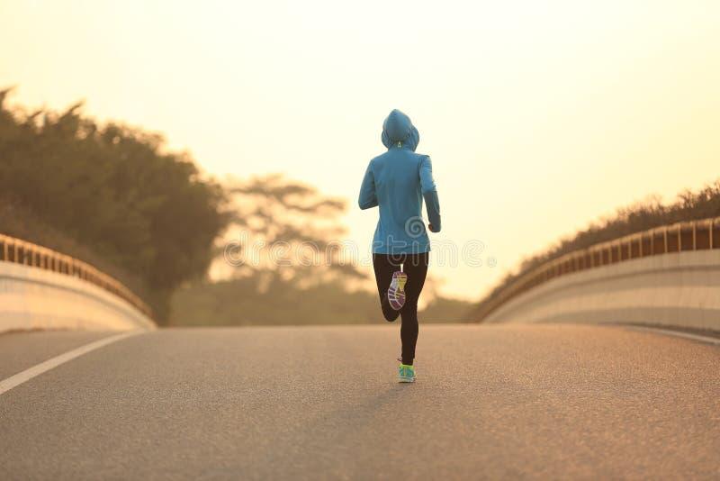 Funzionamento dell'atleta del corridore della donna di forma fisica sulla strada di alba immagine stock
