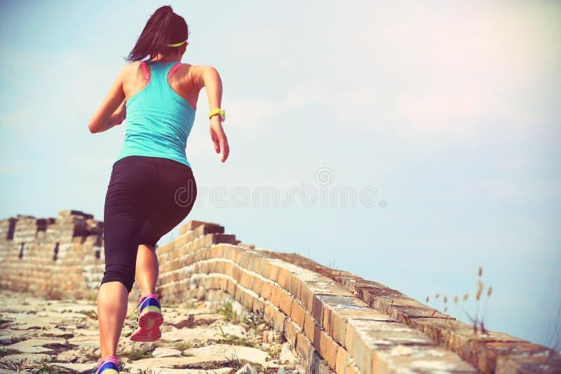Funzionamento dell'atleta del corridore della donna sulla traccia alla grande muraglia cinese fotografia stock