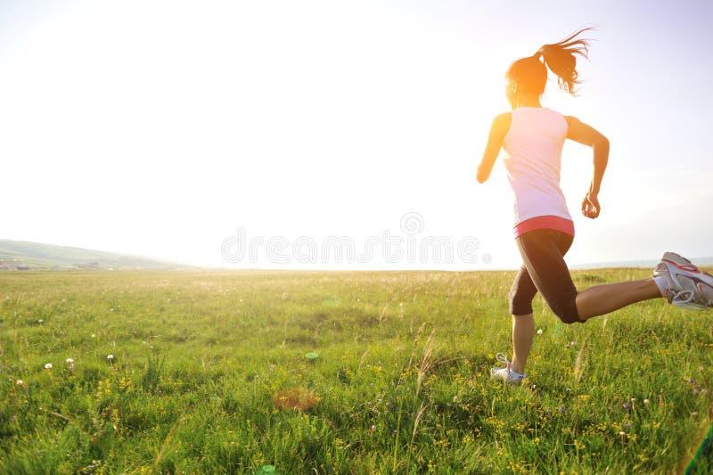 Funzionamento dell'atleta del corridore sull'erba immagine stock libera da diritti
