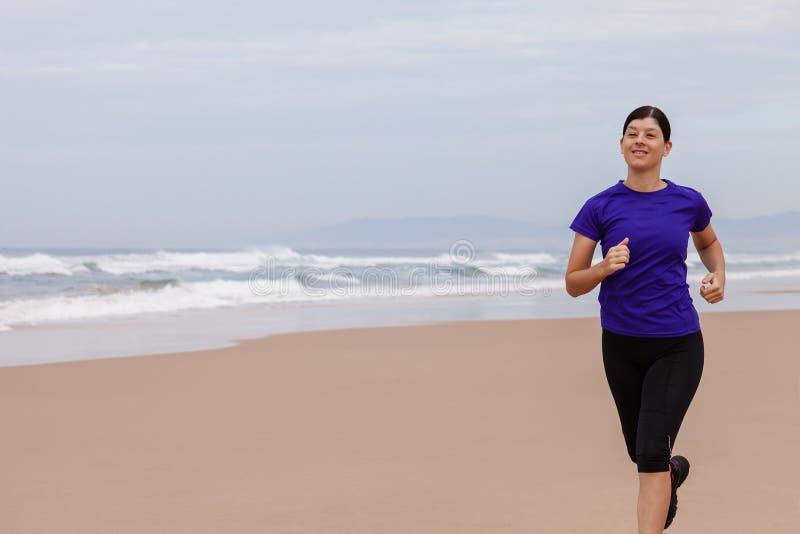 Funzionamento dell'atleta femminile alla spiaggia fotografia stock