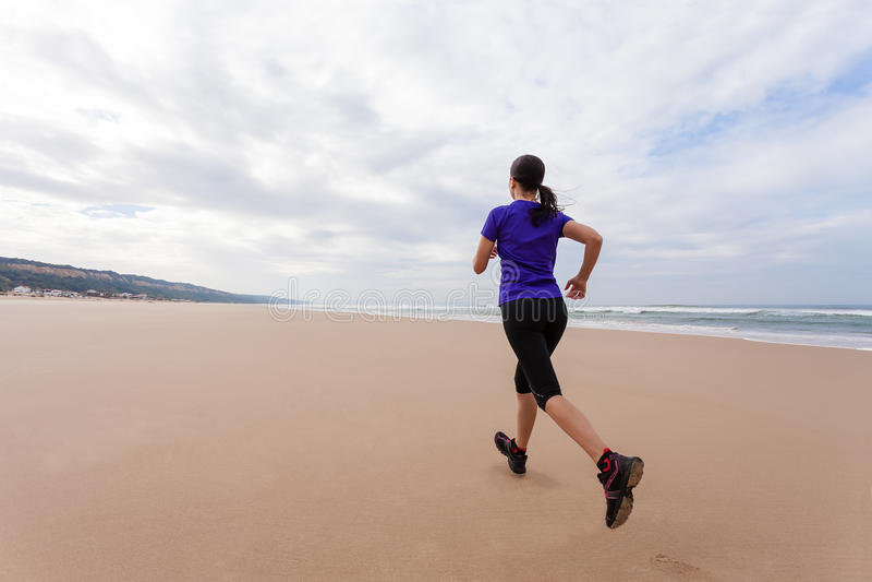Funzionamento dell'atleta femminile alla spiaggia fotografie stock